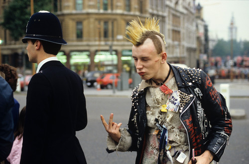 Punk giving the V sign to a policeman, London, Britain - 1983